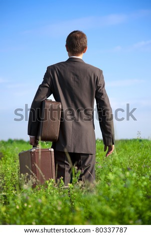 Parting with old two suitcases in his hands the businessman in the field, seen from behind