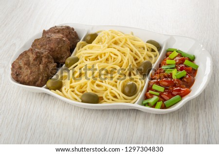 Partitioned dish with spaghetti, cutlet, beans in tomato, green onion and olives on light wooden table #1297304830