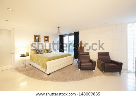 Partly carpeted bedroom with matching leather armchairs in modern house