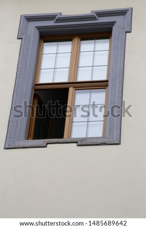 Partly opened sectional window. One quarter of the whole. Fragment of classic architecture facade.