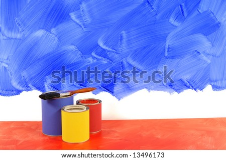 Partly painted blue wall with red floor, paint and paintbrushes