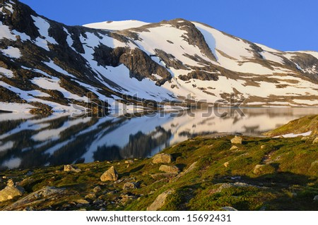 partly snow covered mountain reflects in calm lake