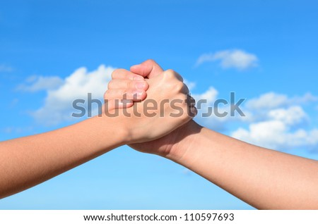 Partner hand between a man and a woman on blue sky background, Teamwork