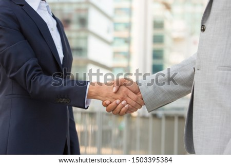 Partners greeting each other in business district. Business man and woman in office suits shaking hands outside. Handshake closeup concept #1503395384
