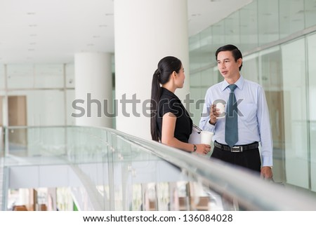 Partners having a conversation in the corridor of a business building