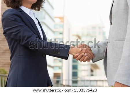 Partners meeting in business district. Business man and woman in office suits standing outside and shaking hands. Partnership concept #1503395423