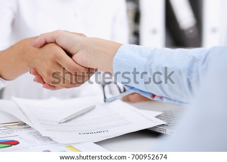 Partnership agreement closeup with man in suit shake hand as hello in background. Friend welcome, mediation offer, greet gesture, participate approval, motivation, strike arm bargain concept