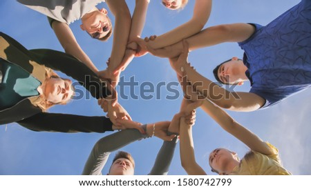 Partnership and unity concept: people holding wrists of each other