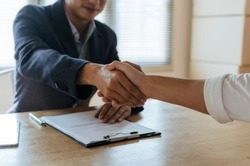 Partnership. business people shaking hand after business signing contract and resume on desk in meeting room at company office, job interview, investor, negotiation, partnership and teamwork concept
