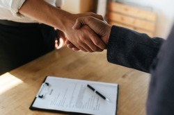 Partnership. two business people shaking hand after business signing contract in meeting room at company office, job interview, investor, success, negotiation, partnership, teamwork, financial concept
