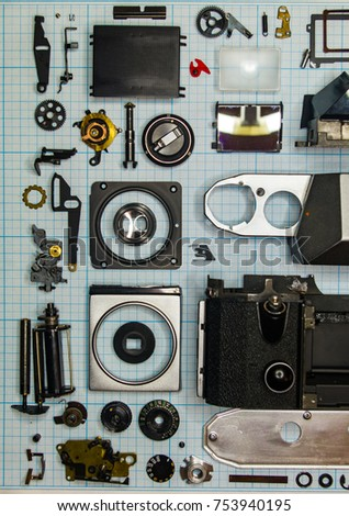 parts are completely disassembled old retro film SLR camera on graph paper, close-up #753940195