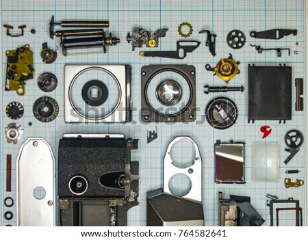 parts are completely disassembled old retro film SLR camera on graph paper, close-up #764582641