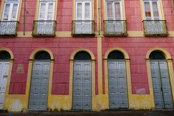 Parts of an antique house facade in old pink and orange yellow, with windows and decorative wrought iron window grilles from around 1900, colonial style in the tropical metropolis of Manaus, Brazil.