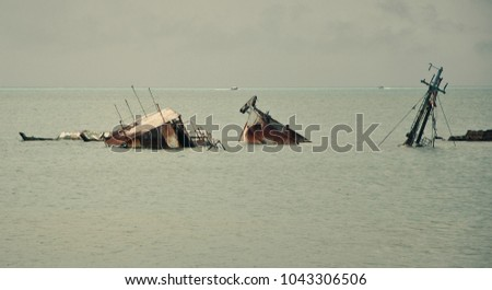 parts of submerged boats in a quiet sea #1043306506