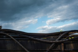 parts of the old mechanism, parts of the hoses of an abandoned excavator under a post-apocalyptic sky with heavy clouds