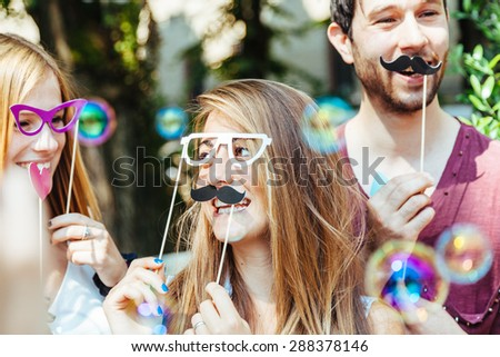 Party! A group of friends, two women and a man have fun at a party in a park with a mustache and fake glasses, joking and talking to each other and playing with soap bubbles in the air!
