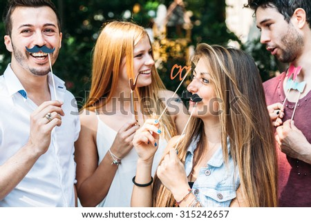 Party! A group of friends, two women and two man have fun at a party in a park with a mustache and fake glasses, joking and talking to each other and playing
