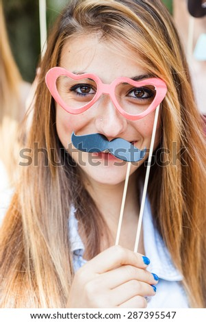 Party! A young blond woman at a party with friends in a park having fun wearing glasses and fake mustache
