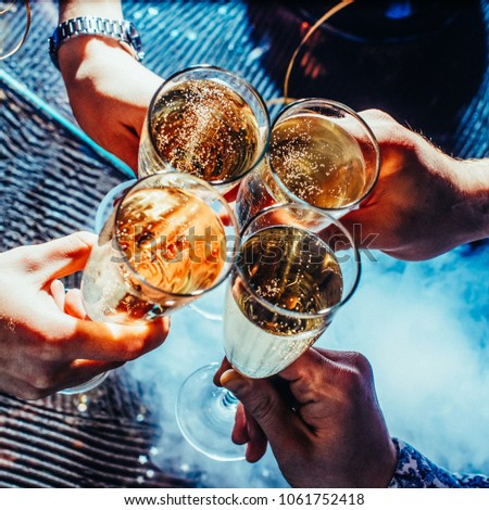 Party and holiday celebration concept. Glasses with champagne in hands. Toned image. with festive ribbons from the top view with the smoke close #1061752418