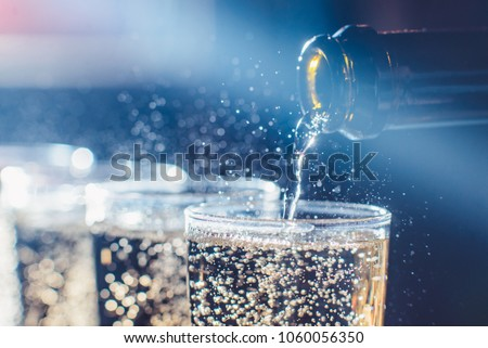 Party and holiday celebration concept. Many glasses of champagne on the table in the restaurant. The process of bottling champagne in glasses. bubbles view with a bottle neck close