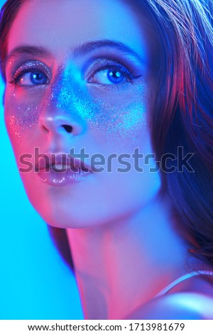 Party and holiday style. Beautiful girl with shiny glitter freckles posing in blue and pink light. Cosmetics and makeup.