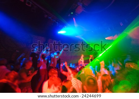 Party at Disco concert full of young people dancing in music and laser show