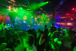 Party at Disco concert full of young people dancing in music and light show