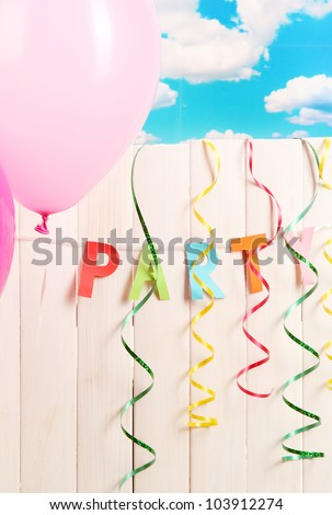 Party. Balloons against a wooden fence on sky background
