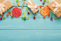 Party border of colorful candies and gifts, top view. Holiday decorations, lollipops and confetti on rustic wood planks with copy space for greeting, invitation or advertising. Birthday background
