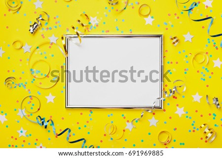 Party, carnival or birthday background decorated silver frame with colorful confetti and streamer on yellow table top view. Flat lay style. Holiday mockup. Greeting card with copy space.