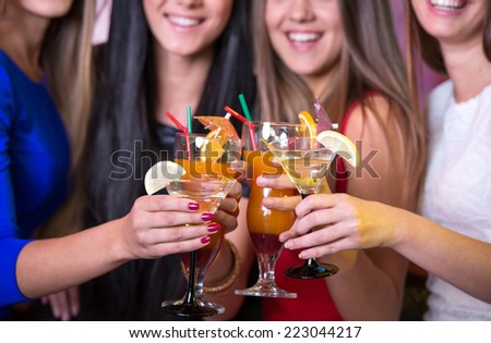 Party, celebration, friends, bachelorette and birthday concept - three beautiful woman in evening dresses with cocktails