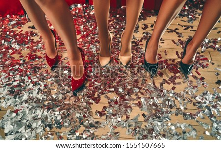 Party concept. Sexy legs of females / women / girls in glamour style shoes with silver luxury confetti on the floor. New Year and Christmas holidays.