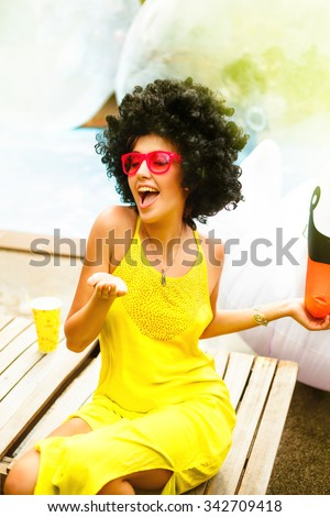 Party concept,woman send kiss with red lips,Eyewear concept.Portrait of a funny hipster girl with trendy glasses and drink alcohol cocktails.Vintage soft image.Duck face emotion.Close up.Indoor shot