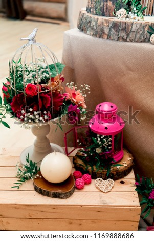 Party decoration in a rustic style. With bird flower cage. Bright pink candle holder standing on a wooden box and sawed wood. #1169888686