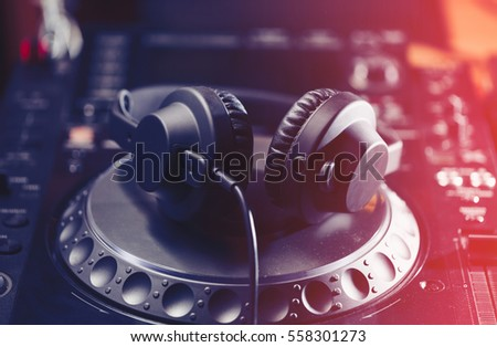Party dj headphones with powerful bass.Equipment for night club.Disc jockey digital cd player turntable.Play music on hip hop parties.Light leak effect.Mix musical tracks on concert event