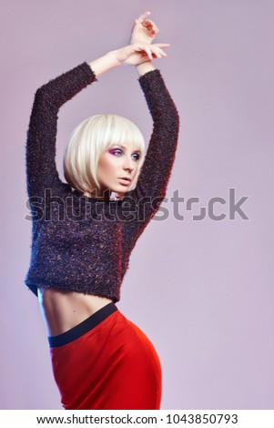Party fashion Blonde woman in dark, shiny shirt and red long skirt with bright, vivid makeup, white background with contrast coloured spots. Fashion makeup beauty and skin care. Daring and erotic look