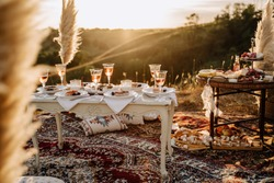Party Festival Table Outdoor for Celebrate Holiday. Drink Glasses and Sweet Dessert on Wooden Vintage Desk, Pillows, Carpet and Dry Plant Decorations. Feast and Gathering, Sunset on Background