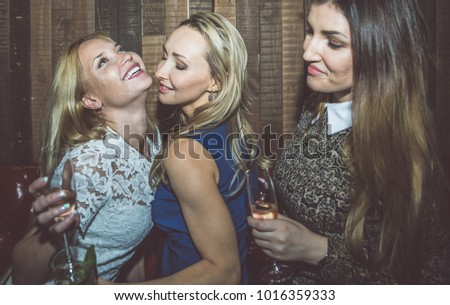 Party girls in a restaurant celebrating with drinks and champagne #1016359333