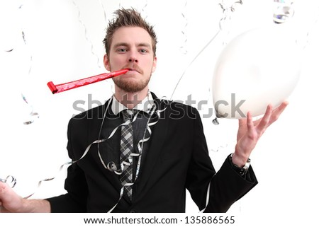 Party guy with partyhat and party blower. Wearing a suit. White background.