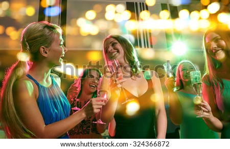party, holidays, celebration, nightlife and people concept - happy young women with glasses of champagne in club #324366872