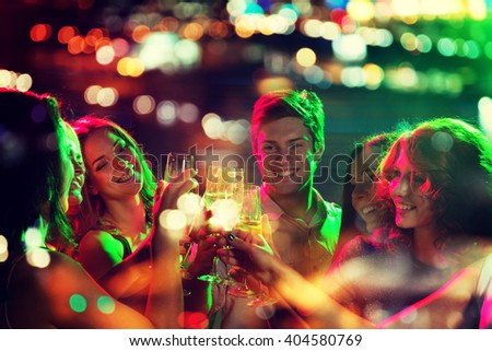 party, holidays, celebration, nightlife and people concept - smiling friends clinking glasses of champagne in night club with holidays lights