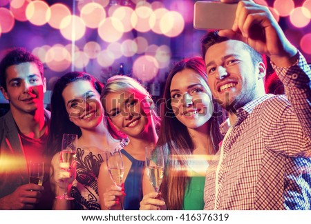 party, holidays, technology, nightlife and people concept - smiling friends with glasses of champagne and smartphone taking selfie in club #416376319
