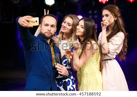 party, holidays, technology, nightlife and people concept - smiling friends with glasses of champagne and smartphone taking selfie in club #457188592