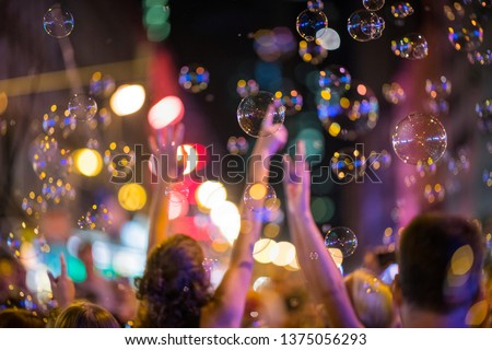 Party in Frankfurt am Main, Germany, (Bahnhofsviertel) railway station quarter night, in the red light quarter many people celebrate together and are happy about many soap bubbles in the evening.