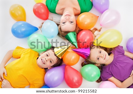 Party kids and their mother laying among colorful balloons