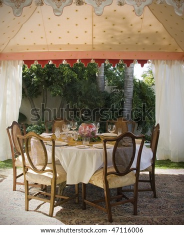 Party lunch, wedding or dinner tent in suburb garden with table and chairs