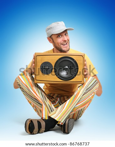 Party man with wooden speaker on blue background
