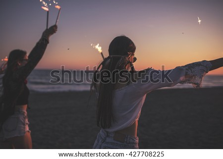 Party on the Beach by night. Leisure Happiness Concept. Silhouette of two friends with firecracker