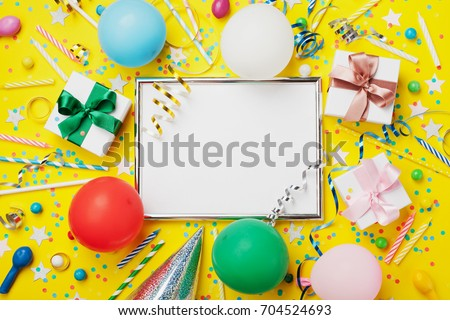 Party or birthday background. Frame with colorful balloon, gift box, carnival cap, confetti, candy and streamer on yellow table top view. Flat lay. Holiday mockup. Greeting card with copy space.