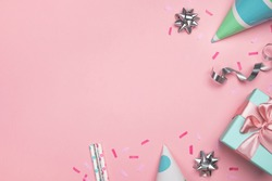 Party or birthday background. Gift box, carnival caps and festive decorations on pastel pink surface. Top view, flat lay, copy space